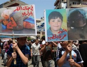Protestas por Hamza al Khatib mostrando sus fotos antes y después de morir torturado.