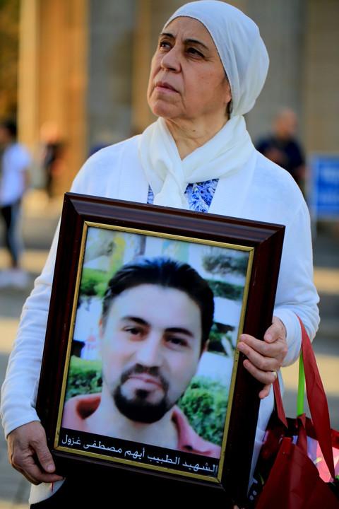 Mariam al-Hallak sostiene un retrato de su hijo Ayham